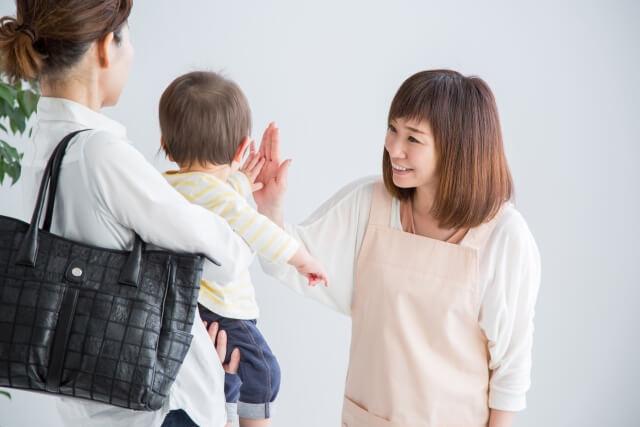 赤ちゃんを見送る保育士