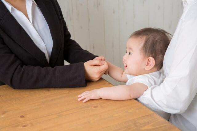 赤ちゃんを挟んで会話する保育士