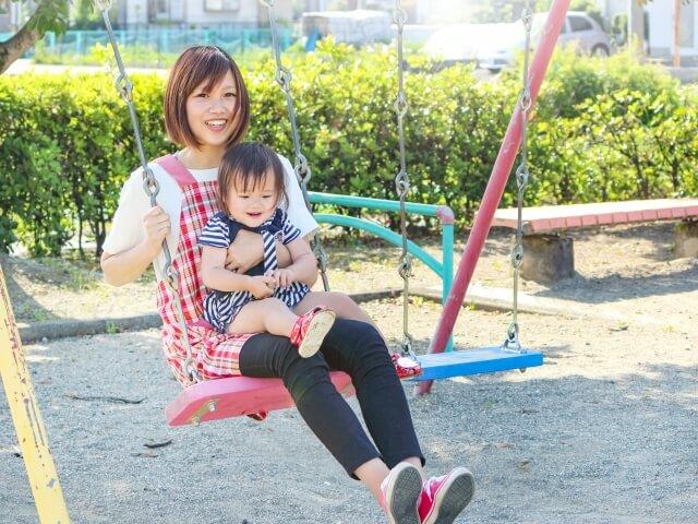 ブランコで遊ぶ保育士と子供