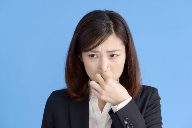鼻を押さえるスーツの女性