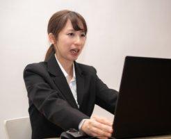 パソコンで調べるスーツの女性
